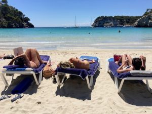 relaxing on the beach in menorca spain with yoga escapes