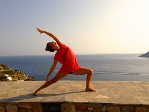 Reverse warrior pose during class in Greece