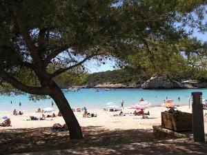 Cala Galdana beach through the trees.
