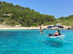 jumping off the sailboat in menorca spain on a yoga holiday