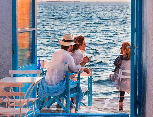people on seats overlooking the sea on a yoga retreat in mykonos little venice