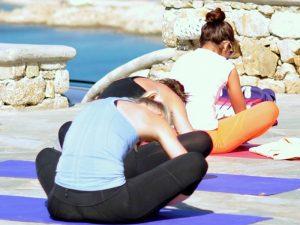 seated forward bend on a luxury yoga retreat on mykonos greece