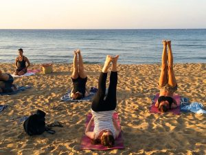 shoulder stand on the beach on a yoga retreat in greece with yoga escapes