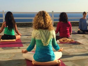 yin yoga and meditation in mykonos greece at sunset with yoga escapes