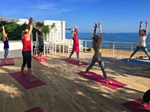 yoga class by the sea on a yoga retreat in crete