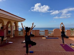 balancing yoga poses by the sea on a yoga retreat in the canary islands